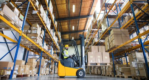 young, person, worker, manager, supervisor, helmet, hard, hat, reflective, vest, safety, work, working, job, inside, indoors, building, warehouse, storehouse, store, shelf, shelves, metal, storage, stock, goods, merchandise, boxes, package, packaging, cardboard, pallet, truck, load, loading, supply, dispatch, logistics, logistic, industry, industrial, forklift, fork, lift, hoist, driver, lowering, male, man